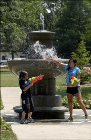 Joseph Cliff, 9, and his sister, Iris Cliff, 14, both of Lawrence, play around the fountain Thursday in South Park. The city shut down the fountain during Wednesday evening's city band concert because it's a magnet for children, who might get hurt climbing in and around it.