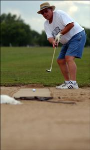 Baker University basketball coach Rick Weaver putts on Baldwin's sand golf course. Weaver and his partner, Journal-World sports editor Tom Keegan, finished with a score of 35 on Wednesday, June 28.