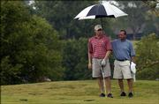 Conrad Roberts, left, and caddy Greg Wyatt stay dry under an umbrella while waiting to take their turn on a soggy green. Participants in the Lawrence Amateuer Golf Assn.'s Big Event played through the rain Sunday at Alvamar Golf Course.