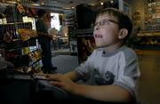 Video game enthusiast Jake Whitebread, 7, Eudora, gets wrapped up playing a Nintendo Game Cube on Thursday afternoon at Game Guy in downtown Lawrence. Jake visited the store with his older brother Tyler Whitebread, 14, who says that he and his brother frequently play video games or spend time on their computer for a few hours a day.