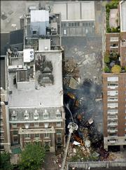New York City firefighters direct water on the remains of a collapsed building on Manhattan's Upper East Side. An explosion rocked the four-story building Monday, causing a fire and eventually a collapse, injuring at least five civilians and 10 firefighters.