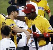 The Mets' David Wright, left, and Philadelphia's Ryan Howard hug during the Home Run Derby. Howard won the event Monday in Pittsburgh.