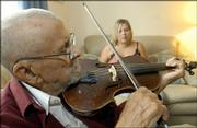 Clyde Thierry, 97, plays his violin as Ashley Holder, a caretaker with Trinity In-Home Care, listens. Holder visits Thierry three times a week to wash dishes, sweep and help keep Thierry company at his Lawrence home, where he lives with his daughter, Daphne Payne, who is 70. Holder's services, provided through the Jayhawk Area Agency on Aging, allow Thierry to stay out of a nursing home.