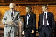 Warren Buffett, left, chairman of Berkshire Hathaway, signs a pledge to give 10 million shares of his company to charitable groups, the majority going to the Bill and Melinda Gates Foundation. The Gateses look on during the signing June 26 in New York.