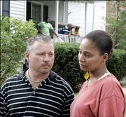 Edris Moore, 36, of St. Louis, right, tries to talk with members of the media Monday about the death of four of her children who drowned Sunday during a church outing along the Meramec River in Ballwin, Mo. Standing next to her is Jeff  Allensworth, senior pastor at the St. Louis Dream Center, which sponsored the outing.