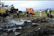 Police officers look at the wreckage of a truck and cars blown up at the site where Chechen warlord Shamil Basayev and other rebels were killed in the Ingush village of Ekazhevo. Basayev was killed Monday when a dynamite-laden truck in his convoy exploded.