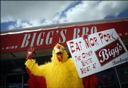 Warren Elliott, A Kansas University junior from Salina, displays a marketing costume and sign that soon will be retired from Bigg's Bar & Grill, 2429 Iowa. The days are numbered for the promotion, which the bar's owner had used for the past year, playing off a Chick-fil-A ad.