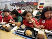 Elena Serrano, 7, second from right, eats an ice cream sandwich during lunch last month at the Four Seasons Elementary School in St. Paul, Minn. The lunch included applesauce, baked tater tots and sloppy joes on wheat buns. A federal law now requires written wellness policies for public schools.