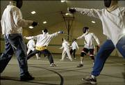Members of the Lawrence Community Fencing Club meet for instruction and practice at First Baptist Church, 1330 Kasold Drive. The club sees an upswing in participation when swashbuckler movies are released.