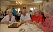Endacott Society members, from left, Rita Haugh, Wiley Mitchell, Gwen Mitchell and Genevieve McMahon visit during a gathering at the Adams Alumni Center. The Endacott Society comprises more than 400 retired faculty and staff members from Kansas University.