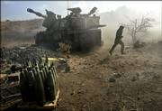 An Israeli gunner runs to reload as an artillery piece fires into southern Lebanon Saturday from a position on the border near Kiryat Shmona, northern Israel. Israel has bombarded Lebanon's airport and main roads after Hezbollah guerrillas captured two Israeli soldiers.