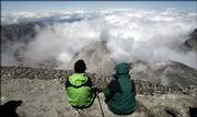Two members of a news media climbing party sit Thursday on the crater rim of Mount St. Helens. The volcano is scheduled to reopen for climbers on a permit-only basis July 21 after being closed since volcanic activity resumed on the mountain in September 2004.