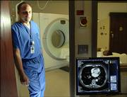 Lawrence Memorial Hospital's 64-slice CT Scanner makes LMH the first hospital in the region to acquire such a Siemens' Somatom Sensation scanner. Marc Schumacher, lead CT technician at LMH, stands between the CT scanner, shown in background, and the monitor in the control room that demonstrates the clarity of the images obtained.