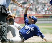 Kansas City's David Dejesus (9) scores from second base, beating the tag from Detroit Tigers catcher Vance Wilson, left. Emil Brown batted in DeJesus during the Royals' 9-6 victory Sunday in Detroit. It was Kansas City's first victory against Detroit this season.