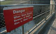 Signs posted along the overlook of the spillway at Perry Lake warn visitors of rapidly rising water levels when the dam is opened. The Army Corps of Engineers began draining water from the reservoir on Wednesday to aid barge traffic on the Missouri River.