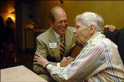 Bob Frederick, left, former Kansas University athletic director, shakes hands with longtime friend Bob Harrison, Lawrence. Harrison celebrated his 90th birthday June 22 with friends and family at the Lawrence Country Club.