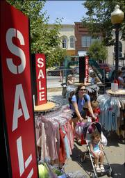 Jenene Marlow, Wamego, and her children shop the clothes racks at Maurice's, 739 Mass. St., during the annual Downtown Lawrence Sidewalk Sale.