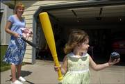 "Elizabether Snider, 3, gets ready to hit the ball as her mother, Stacy Snider, holds her doll ""baby"" and a spare bat outside the family&squot;s home on Monday, July 17. Snider grew up with a learning disability, but now leads a normal life with her husband and two children."
