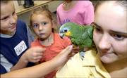 Matthew Stevens, 7, Lawrence, left, Lydia Brown, 4, Eudora, and other children crowd around Olive, a 5-year-old orange-winged Amazon parrot and her owner, Megan Barber, 16, Lecompton, Saturday during the 4-H pet and dog show at the Douglas County 4-H Fairgrounds. Fewer students have participated in the show in recent years, and reports attribute the decline to a difficulty in keeping older youths interested in 4-H because of the demands of sports and jobs.