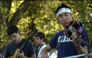 Timmy Wong plays a violin solo with the band Tri Point Paradox during Music for the Masses on Saturday evening at Burcham Park, 200 Ind.