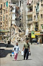 A couple carrying some of their salvaged belongings walk through a destroyed street Saturday in the southern suburbs of Beirut, Lebanon. After more than a week of sustained Israeli airstrikes on the previously densely populated, Hezbollah-controlled area of the capital, few civilians remain, though some ventured back Saturday to salvage belongings.