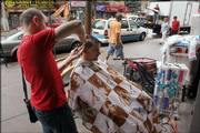 Rocco Aliberti, owner of Hair Fantasy in the Astoria neighborhood of the Queens borough of New York, gives a haircut Saturday to Antonio Vicari on the sidewalk outside the hair salon during the ongoing blackout. Aliberti obtained a generator to provide some power in his store during the blackout.