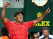 Tiger Woods celebrates after winning the British Open by two strokes over Chris DiMarco. Woods won his 11th major Sunday in Hoylake, England.
