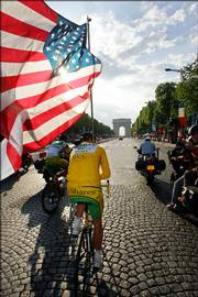 Tour de France winner Floyd Landis waves the U.S. flag as he rides up the Boulevard Champs Elysees after the final stage of the Tour de France. Landis won the 93rd running of the event Sunday in Paris.