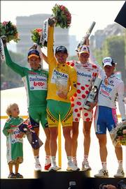 The son of Tour de France top sprinter Robbie McEwen, left, looks up at his dad as the rest of the Tour de France jersey winners acknowledge the crowd. The rest of the group, from left: overall winner Floyd Landis; top colimber Michael Rasmussen; and top young rider, Damiano Cunego.