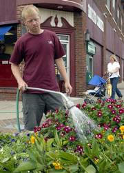 Zac Wininger, a summer employee with the Lawrence Parks and Recreation department and a KU sophomore from Ozawkie, waters a flower planter downtown. Wininger was watering Friday, a day in which a cold front had passed through the area and put an end to a string of 100 degree days.