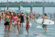 Thousands of people gather at the beach trying to cool off during a record-breaking heat wave Saturday in Huntington Beach, Calif. The triple-digit temperatures were blamed for three deaths in Northern California as the heat prompted dozens of scattered electricity outages.