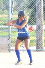 Master Hitter Jasmyn Turner waits at home plate and smiles at comments from her teammates in the dugout on July 18 at Broken Arrow Park. The Master Hitters lost 12-11 to The Flash in both team's last game of the season in their U14 Lawrence Girls Fast Pitch match-up.