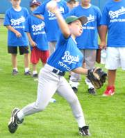 Hunter Taylor fires a throw to a coach at the Royals Youth Clinic. In this drill, former Royals outfielder Brian McRae helps campers work on fielding ground balls and throw them to first base.