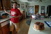 At left, John Brown, an 11-year member of the Palmyra 4-H Club, helps himself to a cake he'd baked the previous night. Baking is one of the contests Brown will enter in the Douglas County Free Fair.
