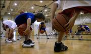 SPENCER GROB, 9, LAWRENCE, does a ball-handling exercise called the pretzel at the Danny Manning Basketball Camp. The camp opened Monday and will continue through Friday at Free State High.