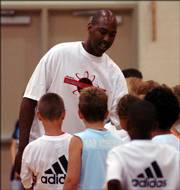 Kansas basketball great Danny Manning makes his way through the lines of young basketball campers dividing the teams Monday morning on the first day of his basketball camp at Free State High School.