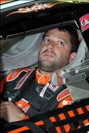 Tony Stewart sits in his car in the garage during practice for the Pennsylvania 500. Stewart was in the center of controversy Sunday when he caused a three-car wreck.