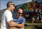 Century School art teacher Tim Holtzclaw, left, hugs muralist David Loewenstein while schoolchildren play in front of the school's mural after its unveiling Monday. The mural was dedicated Monday night.