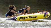 Two girls beat the heat by riding an inflatable tube as it is pulled along the Kankakee River by a motor boat Saturday in Kankakee, Ill. With dangerously hot, humid weather oppressing the Midwest, residents looked for ways to keep cool as heat advisories were issued for parts of northern Illinois.