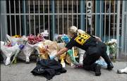 A crime scene investigator rearranges flowers on Saturday in front of the Jewish Federation Building in Seattle so that investigators can close the gate at right after examining the crime scene. Officials stepped up security at both synagogues and mosques Saturday as authorities investigated a shooting at the building that killed an employee and wounded five others, including a pregnant woman.