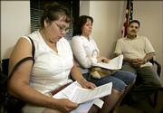 Soledad Salas, left, Maria Arreola, center, and Aristeo Arreola look over paperwork while waiting to meet with a counselor during a recent citizenship workshop at El Centro in Kansas City, Kan. Activists believe thousands of new Hispanic voters could shift the political tide from conservative to liberal.