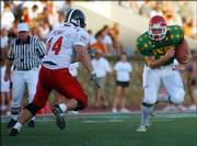 East linebacker Scott Penny (Lawrence High), left, closes in on the West's Taylor Jones.