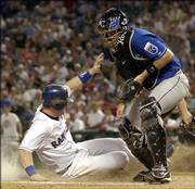 Texas Rangers' Hank Blalock, left, scores against Kansas City Royals catcher John Buck. Blalock scored on a single by Mark DeRosa on Sunday in Arlington, Texas.