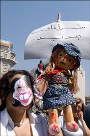 A demonstrator wearing a mask meant to represent U.S. Secretary of State Condoleezza Rice and holding a doll smeared in fake blood joins more than 2,000 Syrian women in a protest in Damascus. The protesters, most of them dressed in black, carried coffins wrapped in black proclaiming the death of peace and the birth of a new Middle East. Placard reads: New Middle East.