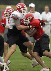 Kansas City Chiefs offensive tackle Kyle Turley, left, blocks Jimmy Wilkerson. The Chiefs held practice in the rain Tuesday in River Falls, Wis.