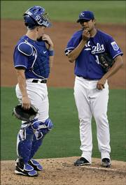 Royals catcher John Buck, left, and pitcher Jorge De La Rosa meet on the mound before De La Rosa was taken out of the game in the second inning. The Twins played the Royals on Thursday night in Kansas City, Mo.