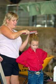 Lexia Jamison, 7, Perry, waits as her mother Judy Jamison fixes her hair before the Bucket Calf Show on Thursday in the livestock barn at the Douglas County Fair.