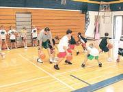 Former Kansas University All-American Nick Collison, left, leads a dribbling drill at his basketball camp. Collison's camp took place July 25-28 at Wichita Collegiate High.