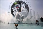George Alvarez cools off with his golden retriever, Captain Ron, in the Unisphere fountain at Flushing Meadows Corona Park in the Queens borough of New York. After two days of triple-digit temperatures, the region was in for another day of steamy weather Thursday.