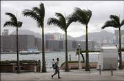 A resident walks through the wind near the waterfront Thursday in Hong Kong. Hong Kong raised its storm alert Thursday as Typhoon Prapiroon, strengthening from a severe tropical storm, moves toward the coast of Guangdong in southern China.
